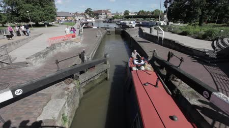 local de nascimento : Stratford upon Avon, UK - JUNE 8, 2014: Unidentified boat travelers going through the canal lock from the River Avon. Stratford is major tourist atraction as its birthplace of William Shakespeare