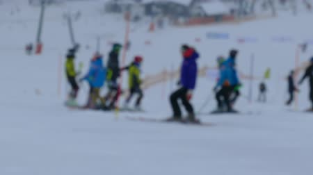 Unrecognisable skiers skiing in the slope of ski resort. Defocused ungraded 4k footage