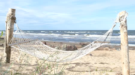 Empty swinging hammock in a sandy beach with wavy sea water in the background Wideo