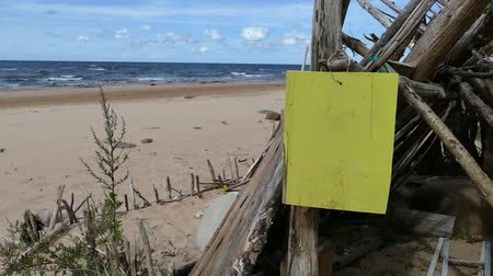improvised : Improvised driftwood Beach shelter hut at sandy seaside with hanging empty yellow signboard Stock Footage