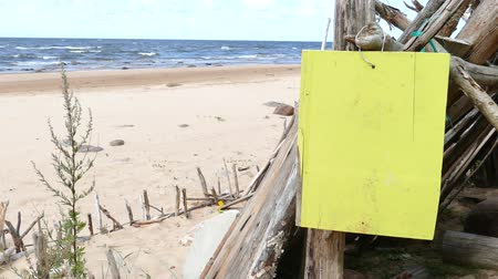 driftwood : Improvised driftwood Beach shelter hut at sandy seaside with hanging empty yellow signboard Stock Footage
