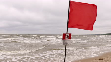tenger : Red warning flag forbidding to swim on the beach in Palanga, Lithuania.