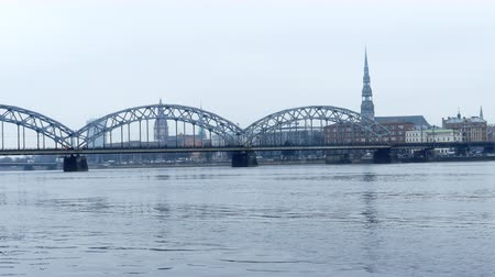 water rail : Iron Railway bridge over River Daugava with Riga Old Town skyline in background Stock Footage