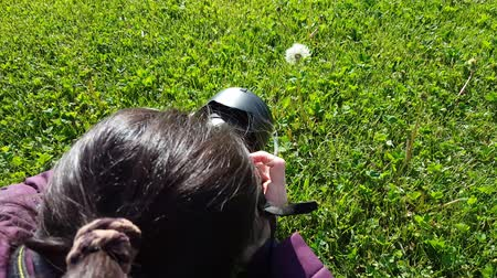camera move : Female photographer using DSLR camera on grass, shooting dandelion Stock Footage