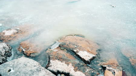 Close up of rocks in a frozen pond in a cold winter day