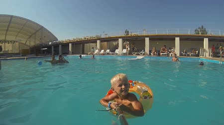 Genichesk, Ukraine - August 30, 2017: Little boy makes selfie photo with selfiestick while swimming in a pool Stock Footage