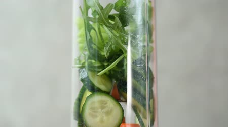 Close-up of ingredients in a blender for a healthy detox cocktail. Cucumbers, greens, protein, milk. Blending cooking.