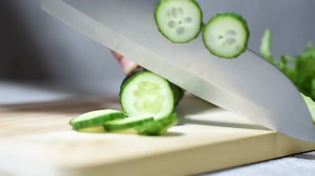 shred : Female chef slicing fresh cucumber with a knife on wooden board, vegetables