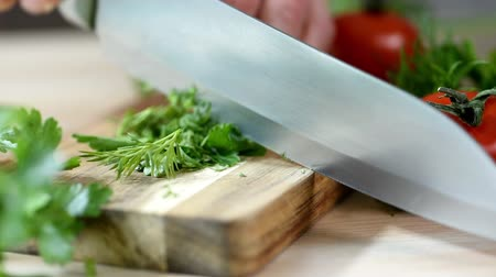 Woman is cutting parsley, greens knife on wooden board.
