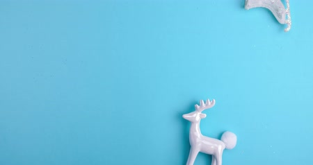 gif : Minimal Motion art. Pattern white Christmas decorations, gifts and snow on a blue background.