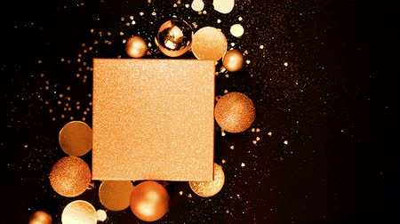Creative concept of Christmas and New Year background, flickers and glitters. Gold gift box and holiday decor with glitters on a black background. Copy space