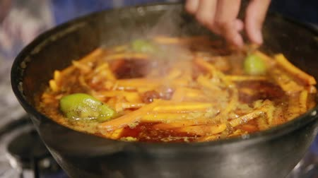 eklemek : Cooking pilaf, shef removes garlic and green chili peppers from cast-iron kettle Stok Video