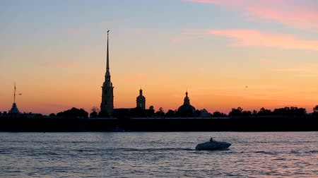 moorage : silhouette of Peter and Paul fortress against the backdrop of the setting sun
