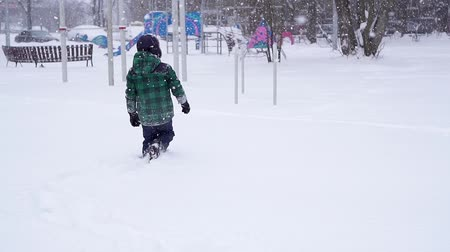 hófúvás : Beautiful joyful preschooler boy runs away through deep snowdrifts.