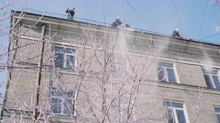 swabber : public service employees dump snow from the roof of the residential building
