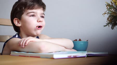 erudite : charming 6 years boy spoiling after reading the book and eating dried fruits Stock Footage