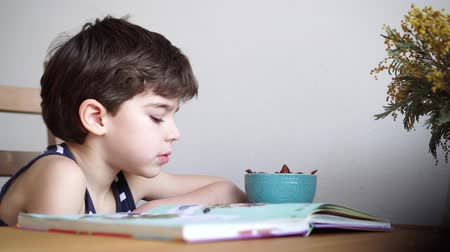 pictured : charming 6 years boy reading the book and eating dried fruits