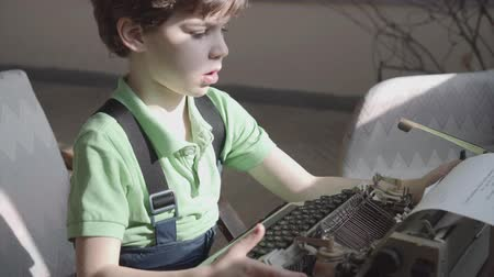 yazar : Pleased little six-year-old boy studies the work of an old typewriter.