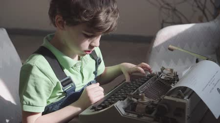 Pleased little six-year-old boy studies the work of an old typewriter.
