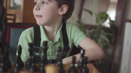 a six-year-old boy arranges figures on a chess board Стоковые видеозаписи