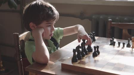 escolha : six-year-old boy arranges figures on a chess board
