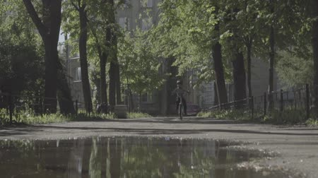 child rides a bicycle over a puddle in summer day. Slow motion. Reflection Стоковые видеозаписи
