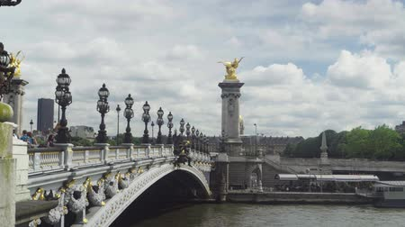 View of the Alexander III Bridge, cloudy sky, many people. Paris