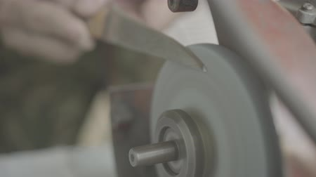 man sharpens a knife on a grindstone, close-up