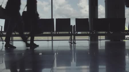 silhouettes of legs of hurrying passengers with suitcases at the airport Stok Video