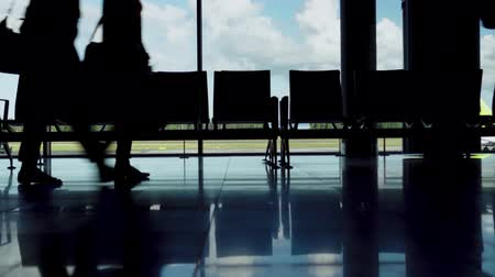 silhouettes of legs of hurrying passengers with suitcases at the airport 動画素材