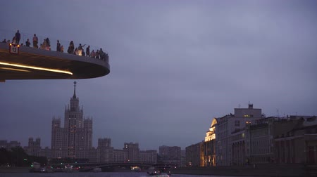 stalinist : People walk on the viewpoint of Zaryadie park, high-rise on Kotelnicheskaya emb