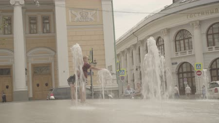 anlamlı : Happy boys play in fountain near the Gostinniy Dvor in Moscow Stok Video