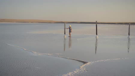 Slim sexy girl enjoying sunset, walks between wooden salt pillars of a salt lake