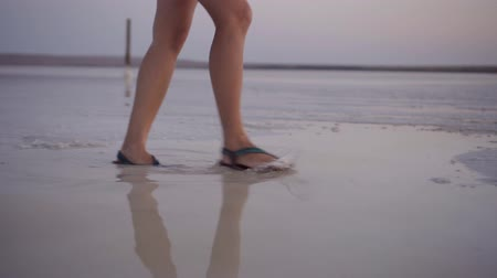 lanscape : girl in green sandals splash through the puddles of salt lake at sunset time