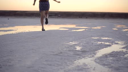 girl in green sandals splash jump through the puddles of salt lake at sunset time