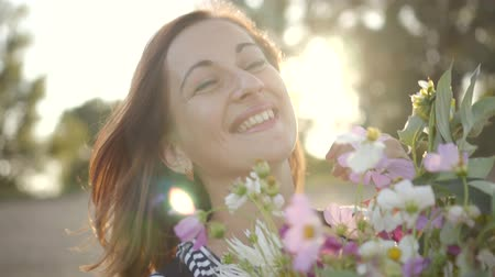 Portrait of beautiful young woman smiling and holding bouquet of wild flowers.