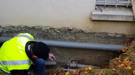 culvert : The plumber is preparing the replacement of the drain pipes in the foundation of the house. Stock Footage