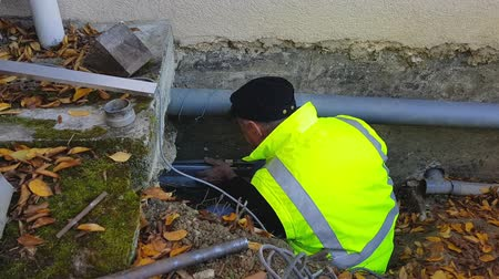 culvert : The plumber man checks the slope of the drain pipes in the foundation of the house.