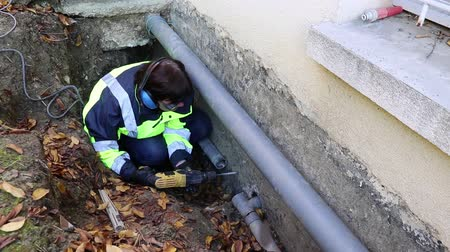 culvert : A woman plumber drills a hole in the outer wall of the house to fix the plumbing pipes. Stock Footage
