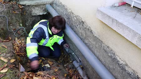 culvert : A woman plumber checks the horizontal position of the water pipes for fixing.