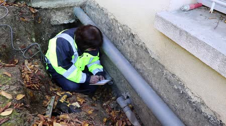 culvert : The woman plumber calculates the size of the water pipes for replacement outside the house.