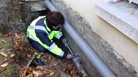 culvert : A female plumber makes measuring water pipes for replacement outside the house. Stock Footage