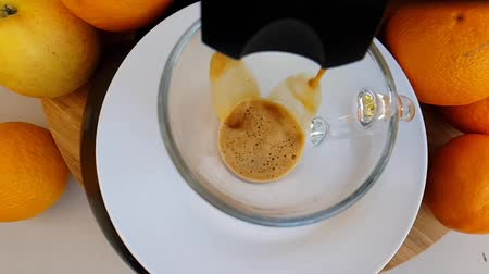 nespresso : Freshly prepared coffee for a coffee maker and fills a transparent cup against the background of the fruit. The start of the action.view from above. Slow motion. Stock Footage