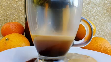 nespresso : Freshly prepared coffee poured from the coffee maker into a transparent cup. Part of the coffee is pouring past the cup. The end of the action. Side view. Slow motion.