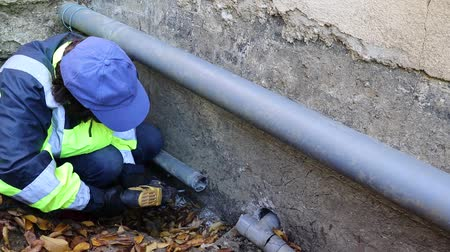 culvert : A woman conducts plumbing in difficult conditions in a narrow pit. The drain pipe burst under the foundation of the house. To replace it, the drill has a hole for fastening. Stock Footage