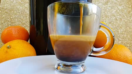 nespresso : Freshly prepared coffee for a coffee maker and fills a transparent cup against the background of the fruit. The end of the action. Side view. Slow motion.