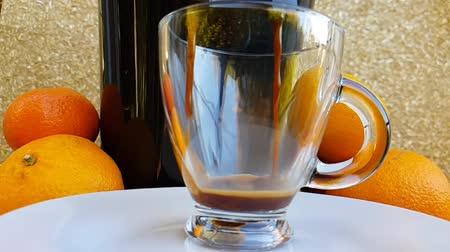 nespresso : Freshly prepared coffee for a coffee maker and fills a transparent cup against the background of the fruit. The start of the action.side view. Slow motion.