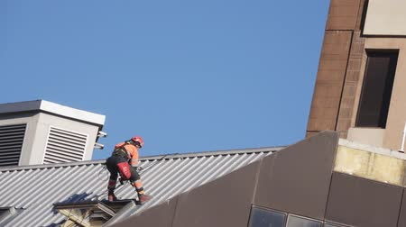 tető : A construction worker is carrying out repairs on a sloping roof. The worker in special clothes is insured with ropes from falling. Stock mozgókép