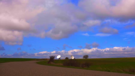 ss : A satellite dish in a field under blue sky.