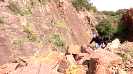 dağcı : An adult man and woman climbs over the piled stones in the mountains.. Stok Video